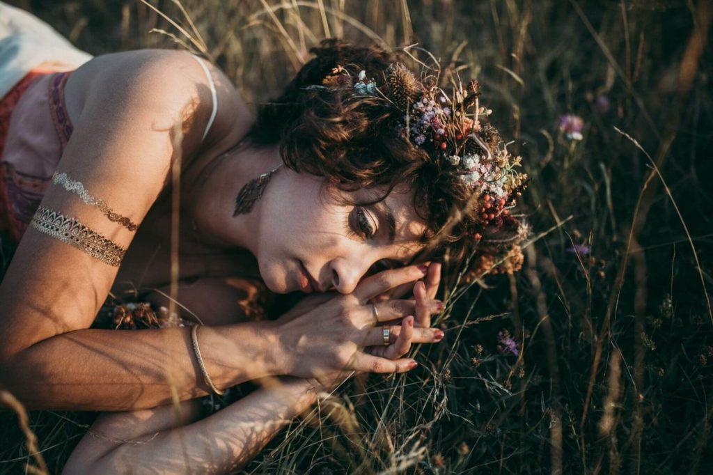 Brautstyling - Braut mit Haarschmuck liegend im Gras